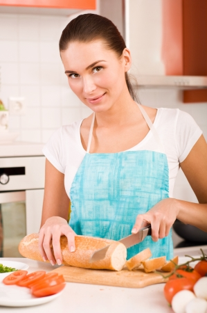 woman knife: Woman cutting bread on the kitchen
