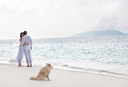 Picture of romantic young couple on the sea shore with dog photo