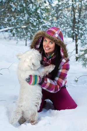 cute westie: Happy woman with dog in winter forest