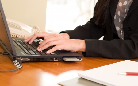 Close up of woman hands typing on laptop photo