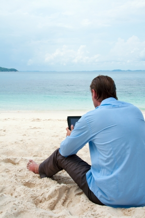 Business man sitting and working on the beach with tablet computer photo