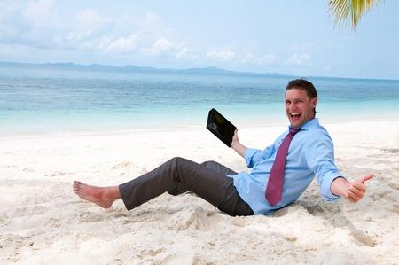 タブレット コンピューターとビーチにして座っている幸せなビジネスの男性