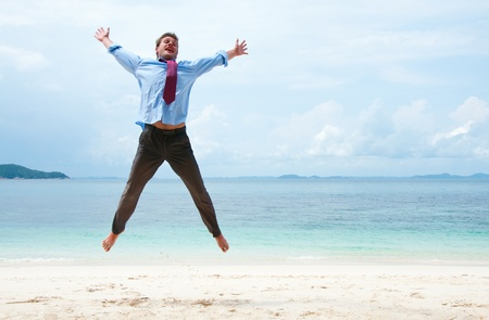 business traveler: Funny business man jumping on the beach