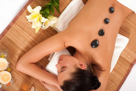hot stone massage: Attractive woman getting spa treatment isolated on white background. Hot Stones Massage Stock Photo