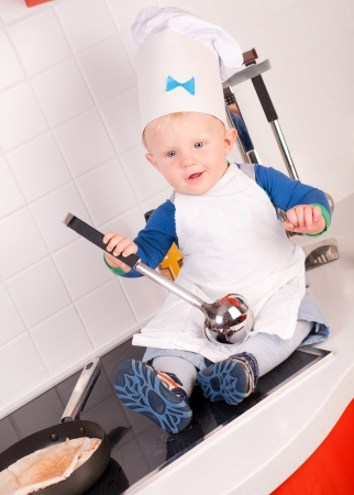 Little baby chef in the cook hat with metal ladle photo