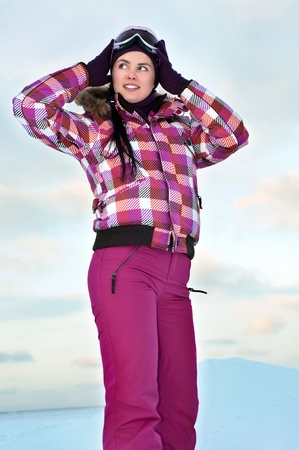 Beautiful young woman wearing skiing suit posing outdoors in winter photo