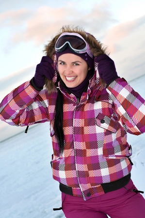 Smiling young woman wearing skiing suit posing outdoors in winter photo