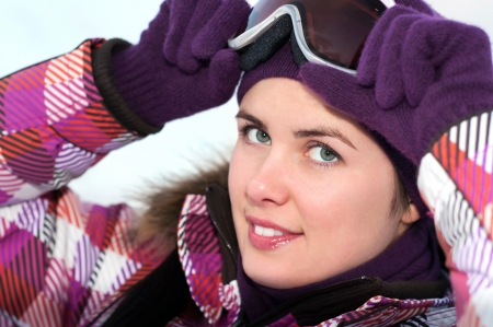 Portrait of smiling happy young woman wearing ski goggles photo
