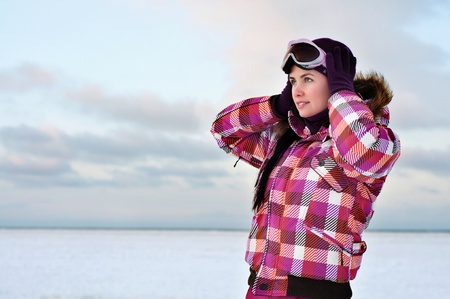 Beautiful young woman wearing skiing suit posing outdoors in winter Stock Photo - 15654214