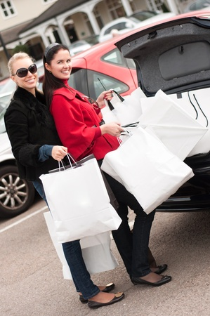 Happy smiling women putting shopping bags into the car  trunk photo
