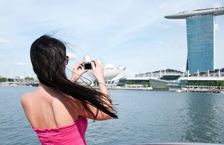 Young woman taking picture of Marina bay hotel in Singapore photo