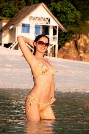 sensational: Young beautiful woman in bikini standing in water during sunset