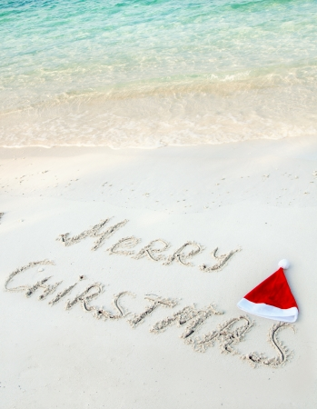 Holiday background - Merry Christmas written on tropical beach sand  photo