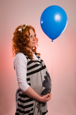 Beautiful pregnant woman holding balloon photo