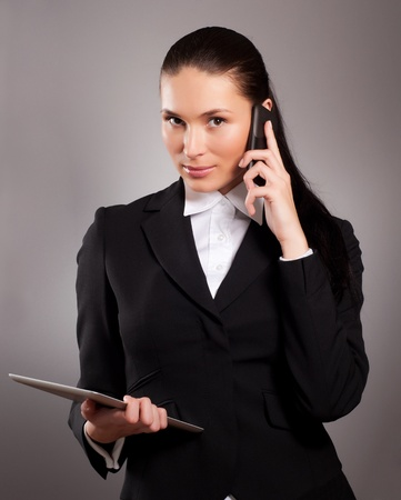 Young businesswoman talking on telephone and using tablet pc photo