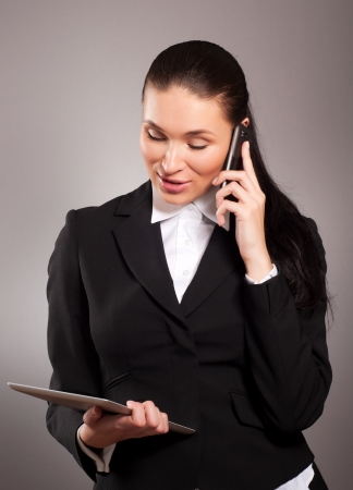 office use: Young businesswoman talking on telephone and using tablet pc Stock Photo