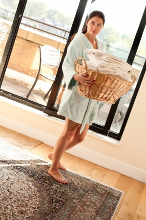 Beautiful young woman carrying a full laundry basket photo