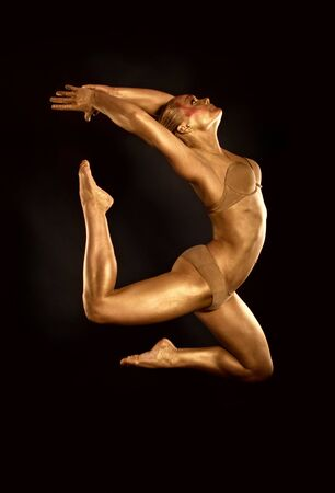 acrobat dancer toned in gold  jumping over black background photo