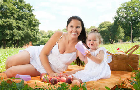 Young happy mother with daughter in the park picnicking photo