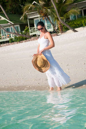 Beautiful woman walking along seaside on tropical beach Stock Photo - 25866999