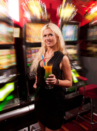 Young woman in Casino on a slot machine with coctail photo