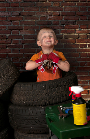 Cute and funny little mechanic with a tire  photo