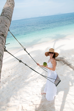 Woman in white dress swinging at tropical beach photo