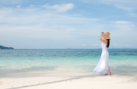 Woman in hat on shoreline at the tropical beach photo
