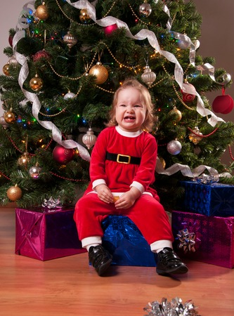 baby near christmas tree: Cute Baby Girl in Santa costume near Christmas tree