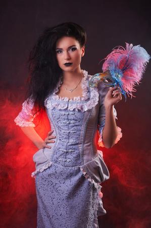 Beautiful Halloween vampire woman aristocrat with venetian mask. on black background