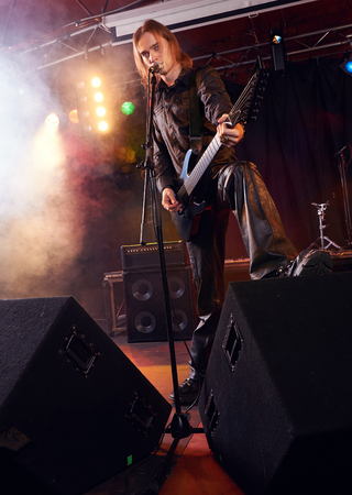 calibrate: Long haired guitarist is performing on stage
