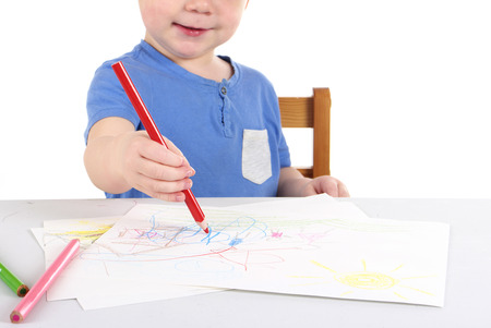 Little boy is drawing the picture. Studio shot
