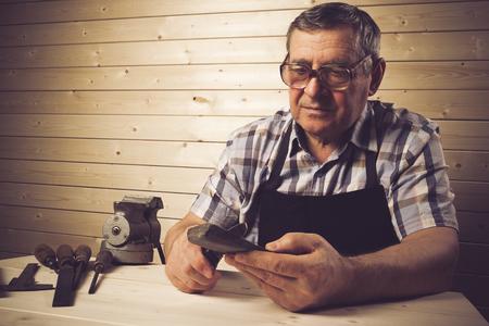 sharpening: Senior carpenter working in workshop