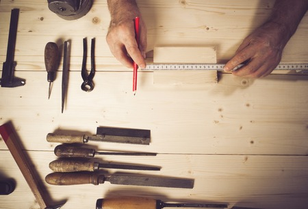 manual measuring instrument: Cropped image of senior carpenter measuring wood Stock Photo