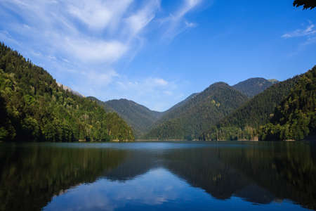 view of the riza lake surrounded with mountains covered with forest under the blue sky