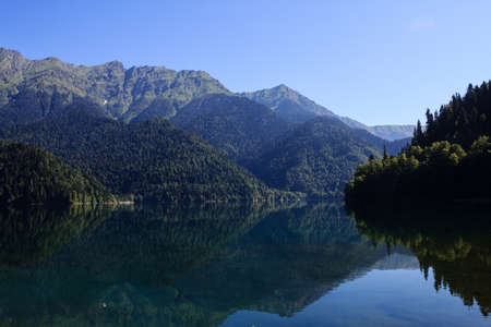 Lake Riza sorrounded with high caucasus mountains mirroring in the water