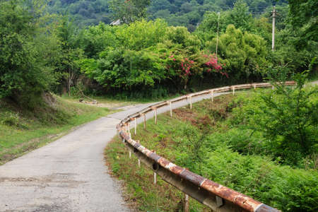 rusty fence: mountain road with rose bush and old rusty fence Stock Photo