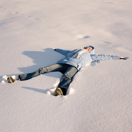 Happy young girl  lying in the snow photo