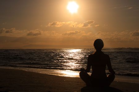 Female meditating on the beach in the morning  at sunrise