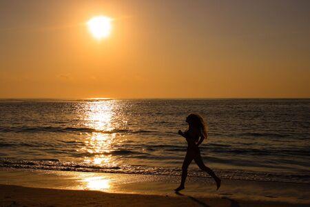 Female running along the beach at sunrise Stock Photo - 1780123