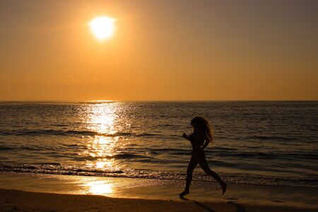 Female running along the beach at sunrise Stock Photo - 1780123