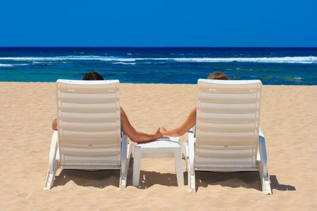 Couple in beach chairs holding hands near ocean photo