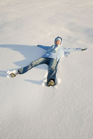 Happy young girl lying in snow photo
