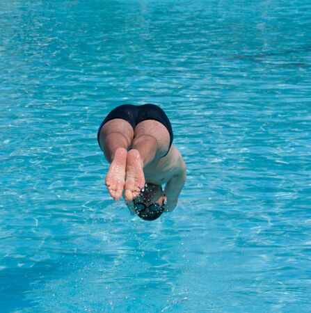 Swimmer jumping into blue water Stock Photo