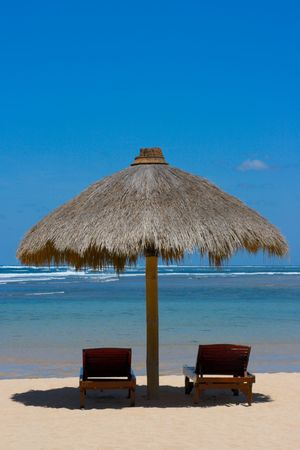 Two lounge chairs under tent on beach photo