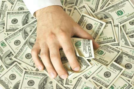 avid: Greedy hand grabs lot of dollars Stock Photo