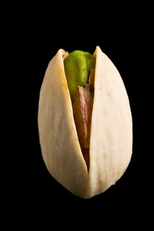 nutshells: Single pistachio nut isolated on black Stock Photo