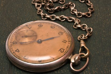 Very old clock with chain lying on rough green  surface - shallow depth of field Stock Photo - 3219543