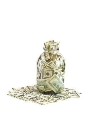 Glass jar full of  hundreds of dollars isolated on white background photo