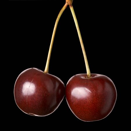 Two cherries hanging isolated on black background Stock Photo - 3367931